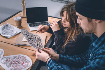 Young couple choosing tattoo design in studio