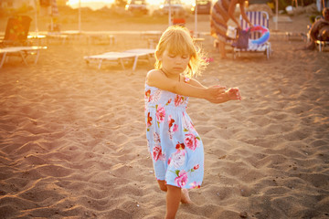 Маленькая девочка танцует на пляже во время заката
