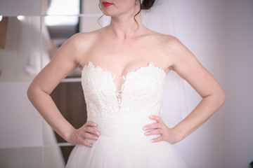 Cropped semi-profile shot of white Caucasian woman with red lips wearing bridal white ballgown and holding hands on the waist, morning wedding preparation and wedding gowns ideas