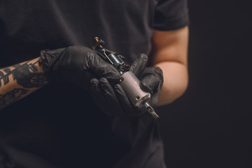Tattoo master in gloves holding ink machine isolated on black