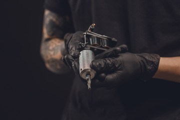 Male hands in gloves holding tattoo machine isolated on black