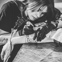 Black and white photo of concentrated female artist in gloves working on arm piece tattoo in studio