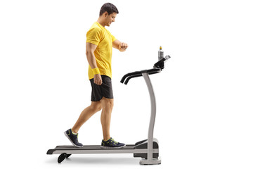 Young man walking on a treadmill and looking at his watch