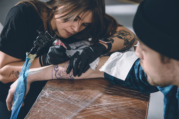 Female tattoo master in gloves working on arm piece in studio