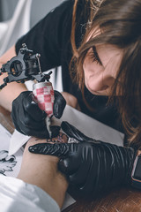 Female tattoo master in gloves with machine working on arm piece