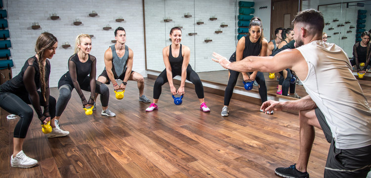 Panoramic view of sporty people training with weights with assistance of their coach at health club.