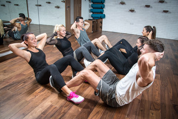 Group of beautiful sporty women and men doing sit ups together on exercise class in health club