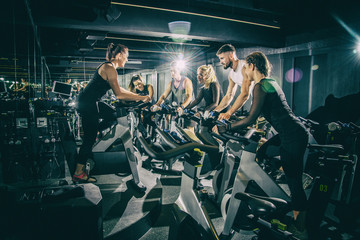 Sporty young women and men riding exercise bikes on cycling class with assistance of female instructor in the gym.