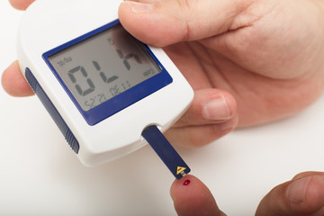 Man with diabetes using a portable glucose meter