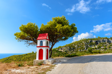 Little chapel and pine tree on coast of Zakynthos island. Greece