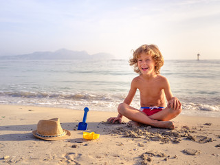 Cheerful boy playing with sand