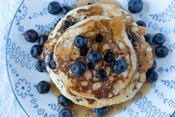 blueberry pancakes with blueberries sprinkles around on flower plate on white tablecloth top view