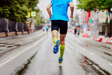 Fototapete - back young runner in yellow compression socks running urban marathon