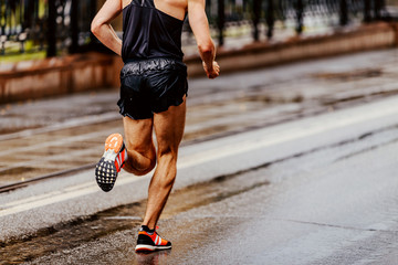 Fototapete - back runner athlete running city marathon on wet asphalt
