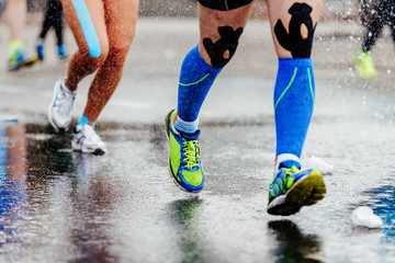 Wall Mural - legs runner in compression socks and kinesiology tape on knees running on water