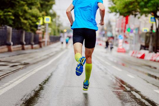 back young runner in yellow compression socks running urban marathon