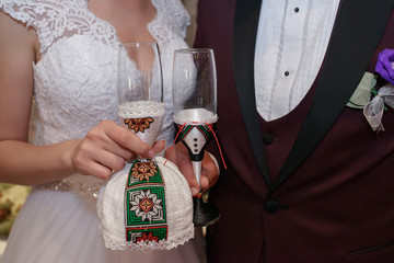 Cropped shot of bride and groom holding playful champagne flutes decorated with ethnic motifs and Romanian folklore's elements at wedding reception