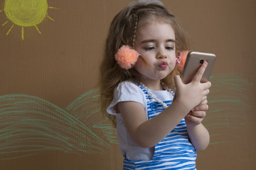 Emotional portrait cute girl makes selfie with a cell phone. Adorable smiling toddler kid taking a selfie photo with smartphone