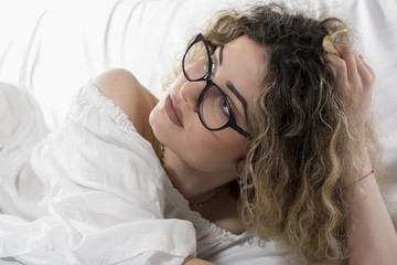 Woman with curly hair and white dress posing on bed