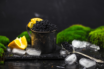 black caviar in a silver bowl with ice and a silver spoon on darck background. silver black caviar . black caviar