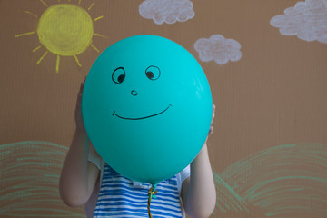 Teenage girl hiding their faces behind smiling balloons. Background of painted sun and white clouds