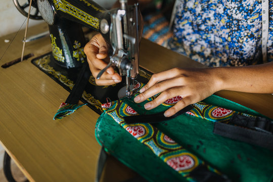 african woman sewing a bagpack close up