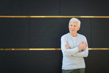 Handsome mature man near dark wall outdoors