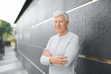Handsome mature man near dark wall outdoors