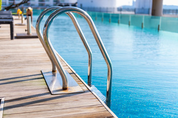 Grab bars ladder in swimming pool on the deck floor