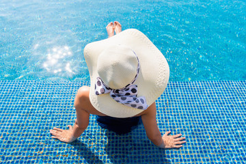 Asian woman relaxing in swimming pool with sunbathe
