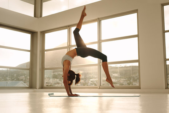 Sporty girl doing handstand yoga asana