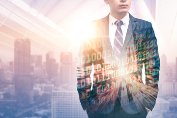 The double exposure image of the businessman wearing a suit during sunrise overlay with cityscape and binary code image. the concept of digital, developers, internet of things and technology