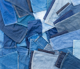 Many pieces of cloth are cut from jeans.