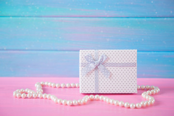 White gift box surrounded by pearl necklace on blue and pink wooden background