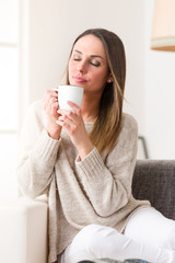 Young woman drinking something hot from her mug