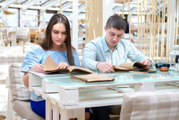 Young girl and guy reading carefully, preparing for the exam
