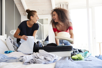 Two Female Friends In Bedroom Packing Suitcase For Vacation