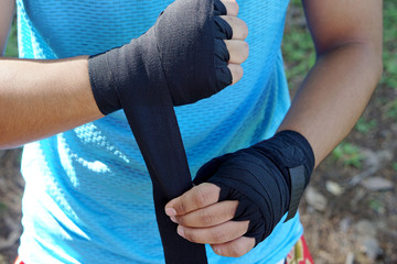 Male boxer wrapping hands with black boxing wraps in the park Strong hand and ready for fight action sport . Close up hand and finger