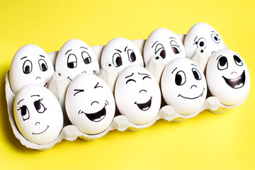 Eggs with drawn cartoon happy faces in box