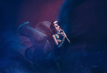 A girl in oriental attire, Queen of the storm. Princess Jasmine. The background is a twist and a strong wind. Studio shooting with mixed light. Artistic Photography