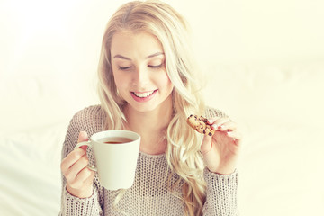 Fototapete - happy woman with tea and cookies in bed at home