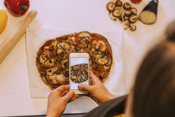 Woman taking picture to delicious pizza.