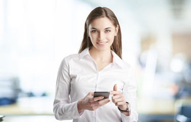 Young businesswoman using mobile phone. Young business woman standing at the office and text messaging before starting business meeting.