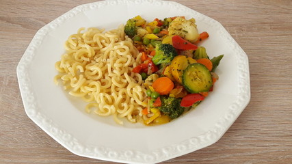 pasta cooked with vegetables in a white plate