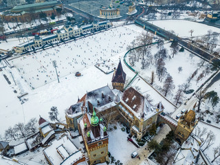 Budapest, Hungary - Aerial skyline view of snowy Vajdahunyad Castle with City Park Ice Rink and Heroes' Square at background on a winter morning