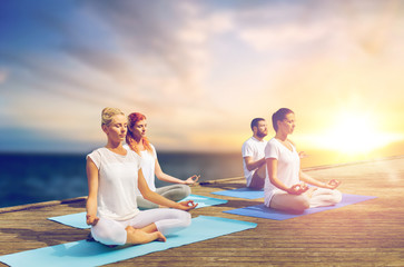 people meditating in yoga lotus pose outdoors