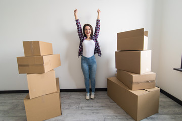 Young happy woman, a student, moved into a new apartment. Unpacks boxes in the new house and raised her hands up as a sign of success.
