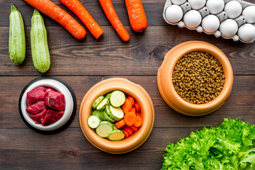 Dry pet food with natural ingredients. Raw meat, vegetables zucchini and carrot near eggs on dark wooden backgroud top view