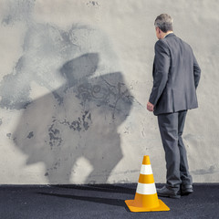 a business man facing a dirty wall