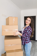 Happy smiling woman carrying carton boxes moving in new appartment